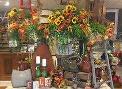 Bright daisies in hanging planters, above a display of furnishings and antiques